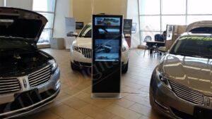 Car dealership's standing indoor digital display.